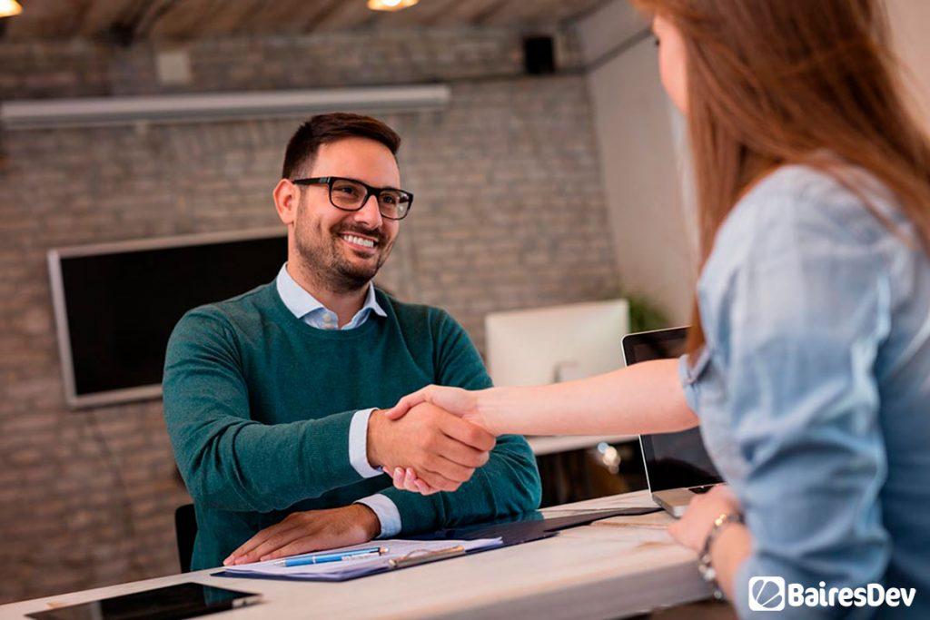 BairesDev recruiter shaking hands with top talent female candidate