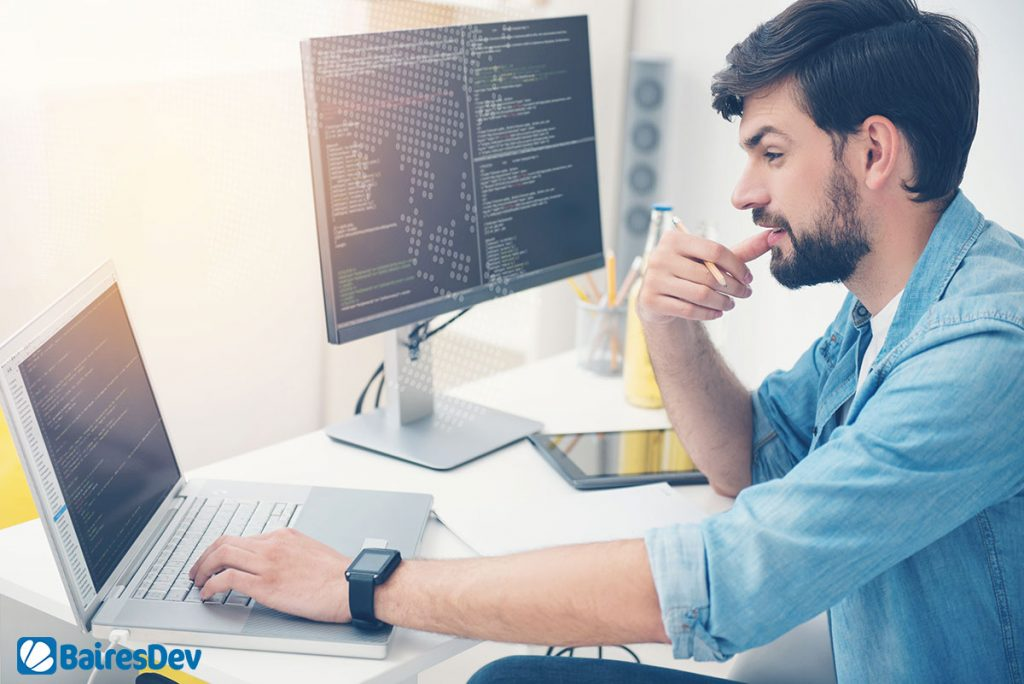 Male software engineer working on python developing trends on laptop and PC